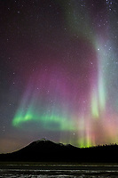 Colorful magenta and green aurora borealis lights the nights sky in Alaska's Brooks Range, Arctic, Alaska