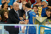 Lionel Messi of Argentina walks past the World Cup trophy and shakes hands with FIFA president Sepp Blatter