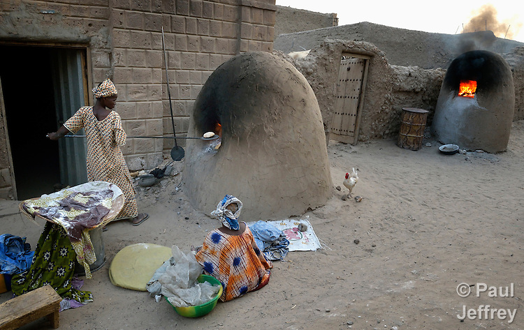 A woman cooks bread early in the morning in Timbuktu, the northern Mali city that was seized by Islamist fighters in 2012 and then liberated by French and Malian soldiers in early 2013. During the jihadis' rule, girls and women could not appear in public unless they were completely covered.