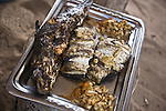 Freshly grilled fish topped with mustard and a side of onions and spices is served at a beachside fish stand in Yoff, a fishing village 30 minutes outside of Dakar, Senegal.