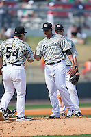Birmingham Barons starting pitcher Frankie Montas (47) hands the ball to manager Julio Vinas (54) as he is taken out of the game against the Tennessee Smokies at Regions Field on May 3, 2015 in Birmingham, Alabama.  The Smokies defeated the Barons 3-0.  (Brian Westerholt/Four Seam Images)