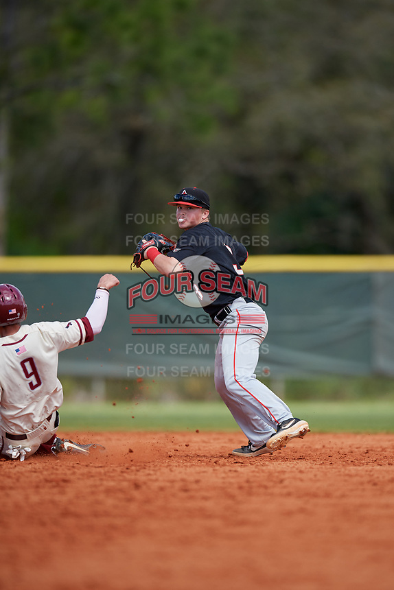 Ball State Cardinals shortstop Noah Powell (3) throws to first base as Chris Skermo (9) slides in during a game against the Saint Joseph's Hawks on March 9, 2019 at North Charlotte Regional Park in Port Charlotte, Florida.  Ball State defeated Saint Joseph's 7-5.  (Mike Janes/Four Seam Images)