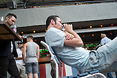 Men watch a TV broadcast of a World Cup football game at an outdoor bar in Budapest.