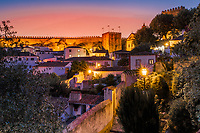 View of the city wall of the beautiful, old village of Obidos, during a colorful twilight, in Portugal Europe