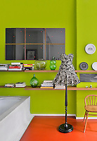 A modern, vibrant lime green bathroom with an orange floor. An old fashioned style lamp standard stands next to the bath and a mirror hangs on the wall above two wooden shelves.
