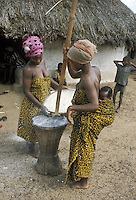 West Africa, Liberia, Kpelle tribe. Women pounding manioc usig mortar and pestle. One women is carrying her baby strapped on her back.