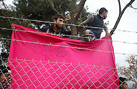 "Pictured: Refugees hold a ""Open the border"" banner Monday 29 February 2016<br /> Re: A crowd of migrants has burst through a barbed-wire fence on the FYRO Macedonia-Greece border using a steel pole as a battering ram.<br /> TV footage showed migrants pushing against the fence at Idomeni, ripping away barbed wire, as FYRO Macedonian police let off tear gas to force them away.<br /> A section of fence was smashed open with the battering ram. It is not clear how many migrants got through.<br /> Many of those trying to reach northern Europe are Syrian and Iraqi refugees.<br /> About 6,500 people are stuck on the Greek side of the border, as FYRO Macedonia is letting very few in. Many have been camping in squalid conditions for a week or more, with little food or medical help."