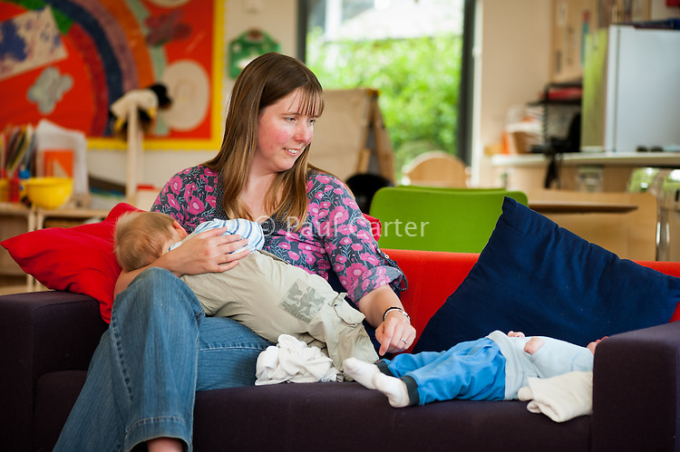 A breastfeeding mother looks after another mother's baby at a drop-in breastfeeding support centre.<br /> <br /> 01/06/2011<br /> Hampshire, England, UK