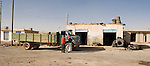 Two men consider a truck that needs repair, outside a garage along the desert highway south from Amman, Jordan.  © Rick Collier
