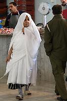 Tripoli, Libya - Libyan Woman Wearing Traditional Furashiya in Fish Market, Rashid Street.  The hem of the colored underneath garment, the irde, is clearly seen.
