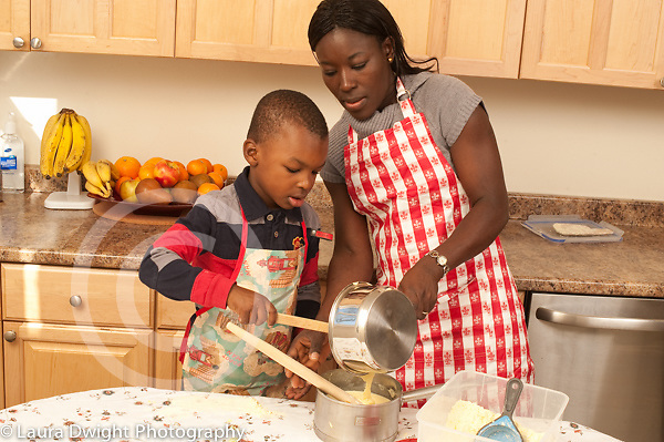 4 year old boy in kitchen with his mother learning to cook traditional cornmeal dish from Togo