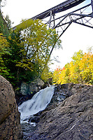 A small waterfall flows under a train trestle on the Dead River. Negaunee Township, Michigan's Upper Peninsula