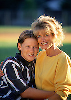 Portrait of a smiling mother and teen son outdoors.