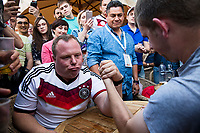 Moscow, Russia, 16/06/2018.<br /> A German supporter arm-wrestles with Russian fans outside a bar in central Moscow during the 2018 FIFA World Cup.