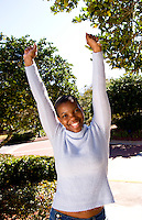 Black African American portrait of woman aged 30 healthy and outdoors in sunshine with short hair and happy