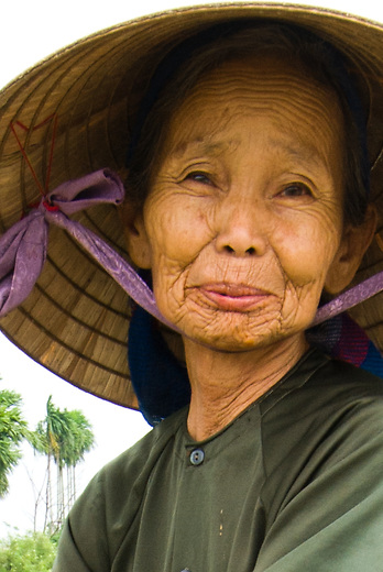 An older VIetnamese woman working in the fields and wearing the traditional Conical Hat.