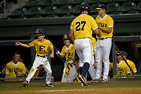 Right fielder Aaron Maher (27) of East Tennessee State is congratulated after scoring a run as 10-year-old Gehrig Skole, son of head coach Tony Skole, does a little dance step in a game against Furman at the Southern Conference Baseball Championship on Saturday, May 27, 2017, at Fluor Field at the West End in Greenville, South Carolina. Furman won, 8-6. (Tom Priddy/Four Seam Images)