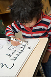 Education Preschool 3 year olds boy writing letters with marker
