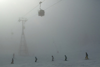 """Switzerland. Valais. Crans Montana. Winter ski resort. CMA ( Crans Montana Aminona) red cable cars are carrying people to the top of the mountain. A Swiss Ski School teacher and his students ( young children) ski down the """"Signal"""" slopes in the fog. Bad weather day. © 2005 Didier Ruef"""