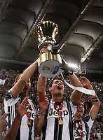 Calcio, finale Tim Cup: Milan vs Juventus. Roma, stadio Olimpico, 21 maggio 2016.<br /> From left, Juventus's Leonardo Bonucci, Alvaro Morata and Paulo Dybala hold the trophy at the end of the Italian Cup final football match between AC Milan and Juventus at Rome's Olympic stadium, 21 May 2016. Juventus won 1-0 in the extra time.<br /> UPDATE IMAGES PRESS/Isabella Bonotto