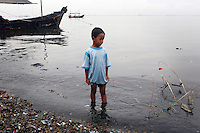 """A young boy looks out onto Jakarta Bay as a fishing boat passes by. According to the Climate Reality Project, """"without flood protection measures, sea level rise could expose up to 6 million Indonesians to annual coastal flooding. The worst of the flooding would occur on the island of Java, where Jakarta is located."""""""