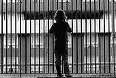 A solitary child looks through railings (posed by model).