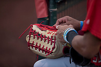 AZL Angels center fielder Jordyn Adams (21) tightens the laces on his custom 44 professional glove during an Arizona League game against the AZL Padres 2 at Tempe Diablo Stadium on July 18, 2018 in Tempe, Arizona. The AZL Padres 2 defeated the AZL Angels 8-1. (Zachary Lucy/Four Seam Images)