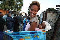 Marthina Korsten waits with her baby Terence (10 months old) in a long line outside a polling station in Diepsloot, Johannesburg to cast her vote in the 2009 general election.