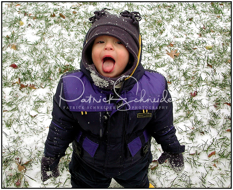 A young boy tries to catch snow on his tongue during a light snowfall in Charlotte, NC. Model released image.