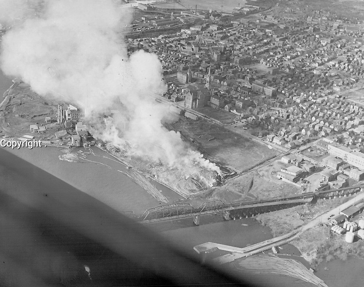 A score of firemen were treated for burns in the raging inferno at Hull Friday night that cut road; rail and tram traffic from an important route and stopped telephone service to a large section of the city. Piled 75 feet high and covering a four-acre area; thousands of cords of pulpwood were destroyed. Aerial photo shows pile smouldering today<br /> <br /> [unknown]<br /> Picture, 1946<br /> <br /> PHOTO : Toronto Star Archives - AQP