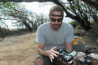 NOAA researcher Dr. Charles Littnan prepares a Crittercam and tracking instrumentation package, which will be glued to the fur of a Hawaiian monk seal as part of the Hoike a Maka project; west end of Molokai, USA, Pacific Ocean