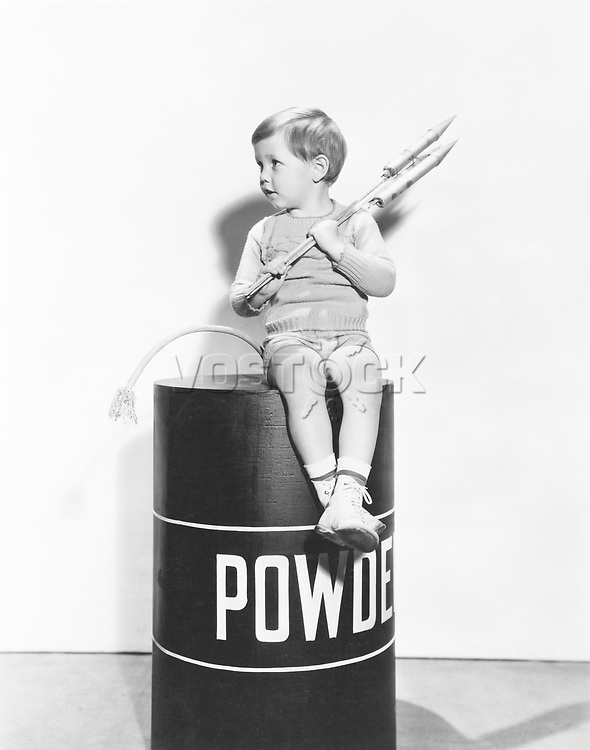 Little boy sitting on powder keg