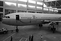 Usine de l'Aérospatiale de Saint-Martin-du-Touch, grand hall de montage. 5 février 1972. Vue d'ensemble de l'Airbus A300 B (vue de côté, partie avant de l'avion) tracté par un tracma ; techniciens autour de l'avion. Cliché pris lors du 1er déplacement tracté de l'avion encore en cours de montage.