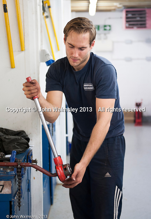 Trainee plumber cutting a thread on a pipe, Able Skills, Dartford, Kent.