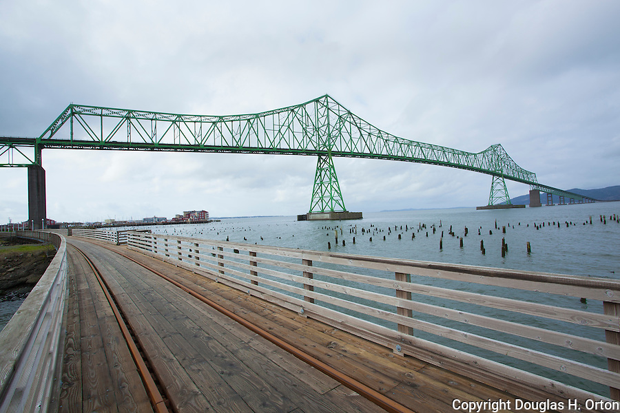 City trolley tracks pass under the Astoria-Megler Bridge, Columbia River, a steel girder continuous truss bridge spanning the Columbia River between Astoria, Oregon and Point Ellice, Megler, Washington, United States.  Total span 14 miles.  It is the longest continuous bridge in North America. Please contact the photographer regarding licensing this image.