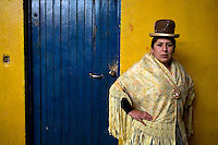 29 year old wrestler Martha La Altena (fighting name), Yenny Wilma Maraz Herrera (real name) poses outside the changing room at the Multifuncional building where every Sunday wrestling takes place. Yenny is a Cholita, a wrestler of native Aymara descent. When Cholitas fight they wear traditional costume: colourful dresses and dark bowler hats. Yenny fights with the lucha libre (free wrestling) group Los Titanes del Ring.