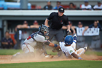Kevon Jackson (11) of the Burlington Royals is tagged out at home plate by Danville Braves catcher Victor De Hoyos (34) as umpire Adam Pierce looks on at Burlington Athletic Stadium on July 13, 2019 in Burlington, North Carolina. The Royals defeated the Braves 5-2. (Brian Westerholt/Four Seam Images)