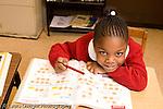 K-8 Parochial School Bronx New York Kindergarten portrait of girl leaning over math workbook horizontal