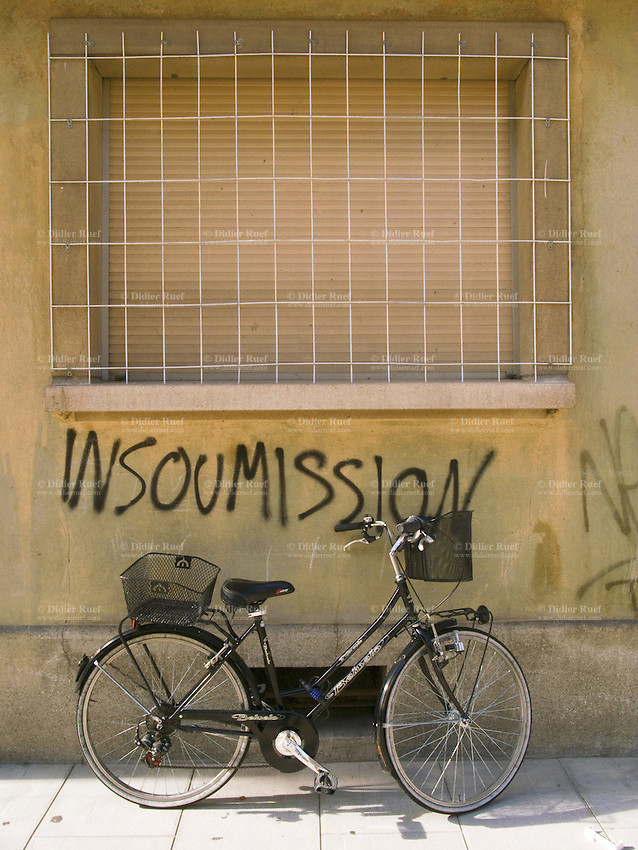 """Switzerland. Geneva. A bicycle for woman is parked under a window railed off from the street. The word """"unsubdued """"is written on the wall. 11.07.09 © 2009 Didier Ruef"""
