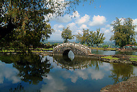 Reflections of an arched bridge in a lake at Queen Liliuokalani Gardens in Hilo on the Big Island of Hawaii.