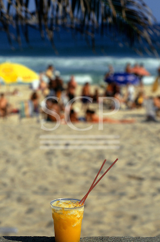 Brazil. A glass of Batida de Maracuja (passion fruit juice & alcohol), with beach back-drop.