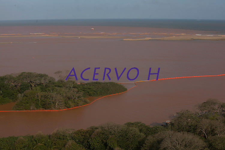A lama trazida pelo rio Doce chega ao litoral do Espirito Santos.<br /> Espirito Santos, Brasil.<br /> Foto Marcello Lourenço<br /> 22/11/2015<br /> <br /> <br /> <br /> A lama trazida pelo rio Doce chega ao litoral do Espirito Santos.<br /> Espirito Santos, Brasil.<br /> Foto Marcello Lourenço<br /> 22/11/2015<br /> <br /> A lama mudou a cor da água do Rio Doce na praia de Regência, onde o rio deságua no mar, em Linhares, Norte do Espírito Santo, na tarde deste sábado (21). Por volta das 16h, a água começou a ficar na tonalidade marrom. Uma barreira de 9 km foi montada para proteger a fauna e flora na região e amenizar os impactos da lama.<br /> O Serviço Geológico do Brasil informou que não tem previsão para que a parte mais densa dos rejeitos de mineração da barragem da Samarco, cujos donos são a Vale e a anglo-australiana BHP Billiton, chegue à foz.<br /> A lama está em três municípios do estado: Linhares, que não usa as águas do Rio Doce para abastecimento da cidade. Baixo Guandu, que passou a usar as águas do Rio Guandu. E Colatina, que há quatro dias parou de usar a água do rio.<br /> O rompimento de uma barragem de rejeitos de minério aconteceu no dia 5 de novembro e causou uma enxurrada de lama no distrito de Bento Rodrigues, em Mariana, na região Central de Minas Gerais