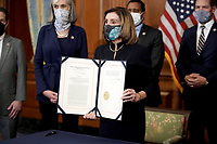 Speaker of the United States House of Representatives Nancy Pelosi (Democrat of California) holds H.R. 24, an article of impeachment against President Donald Trump, after an engrossment ceremony on Wednesday, January 13, 2021 at the U.S. Capitol.<br /> Credit: Greg Nash / Pool via CNP /MediaPunch