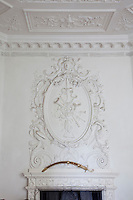 Detail of plasterwork moulding above a fireplace and stucco decoration on the ceiling