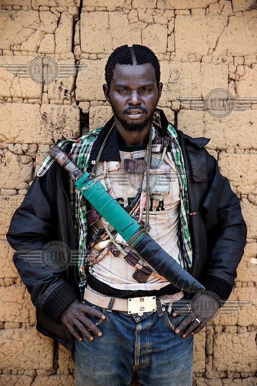 An Anti-Balaka (Anti-Machete) fighter carrying a home-made sword and draped with 'Gris Gris' amulets that confer good fortune and protection on the wearers. They are animist in origin but also worn by both Muslims and Christians throughout west and central Africa. In late 2012 after years of instability and conflict, the Seleka, a predominantly Muslim rebel group, fuelled by grievances against the government, overran the country and, In March 2013, ousted President Francois Bozize, who fled the country. The rebel's leader Michel Djotodia was proclaimed president in August 2013. He disbanded the Seleka in September 2013 but law and order collapsed and ex-Seleka fighters roamed the country committing atrocities against the civilian population. In an attempt to defend their lives and property vigilante groups, calling themselves Anti-Balaka (Anti-Machete), formed to confront the ex-Seleka fighters but soon began to take reprisals against the wider Muslim population and the conflict became increasingly sectarian. By December 2013, with international fears of a genocide being voiced, French led peacekeepers deployed to the country began to act on a UN mandate to disarm the fighters and protect the civilian population. However, they have struggled to contain the situation. Much of the Muslim population, in particular, have been forced into ghettos where they are suffering from food shortages and limited access to healthcare. Often, only a few peacekeepers stand between them and a massacre by vengeful Anti-Balaka militants. UN reports describe 'thousands' killed, while over 600,000 people have been internally displaced and a further 200,000 have fled the county.