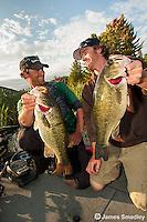 Men hoisting largemouth bass