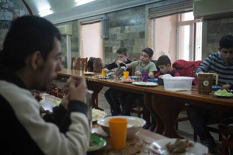 31/10/14. Alqosh, Iraq. Milad (second right) and Wassam (centre) eat lunch at the monastery.