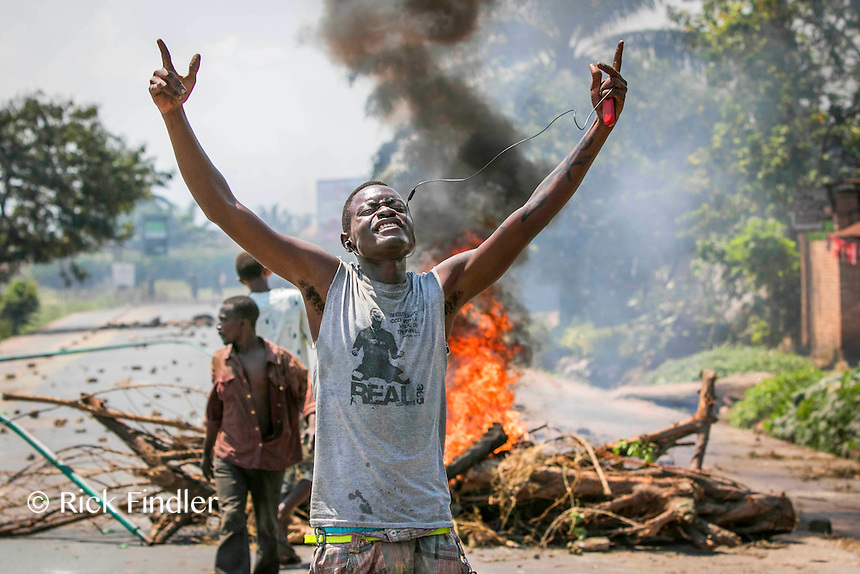 Bujumbura, BURUNDI  03/06/15 A demonstrator celebrates as a road blockade burns behind him. Demonstrations continued today in Burundi's capital city of Bujumbura. Hundreds of people joined together in the streets to make barricades and start fires in protest against President Pierre Nkurunziza trying for a controversial third term as leader. Approximately 90,000 people have fled the unrest which has seen 40 protesters killed by police and army officers. Rick Findler / Story Picture Agency