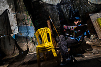 Afro-Colombian market vendor reads the morning newspapers in the market of Bazurto in Cartagena, Colombia, 5 December 2018. Far from the touristy places in the walled city, a colorful, vibrant labyrinth of Cartagena's biggest open-air market sprawls to the Caribbean seashore. Here, in the dark and narrow alleys, full of scrappy stalls selling fruit, vegetables and herbs, meat and raw fish, with smelly garbage on the floor and loud reggaeton music in the air, the African roots of Colombia are manifested.