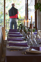 The dining room table decorated and set with flowers and decorative vegetables for dinner guests. A man standing with his back to the camera on the balcony outside the dining room Clos des Iles Chambres d'Hotes Bed and Breakfast Le Brusc Six Fours Cote d'Azur Var France
